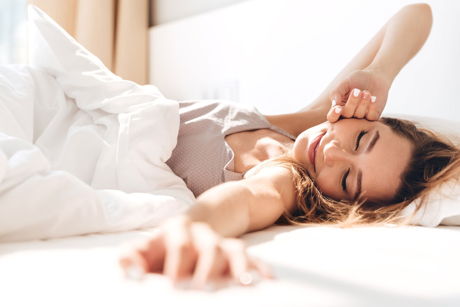 Woman happily waking up after a good night's sleep