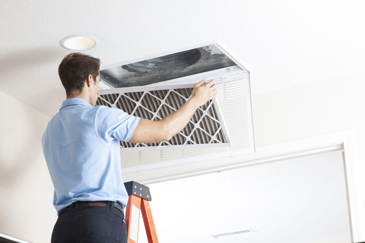 A man changing his air filter every month for allergy season