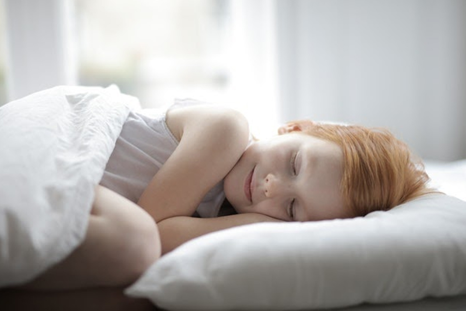 Little girl smiling while sleeping