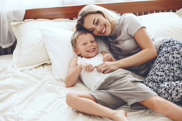 A mom lying in bed with her son