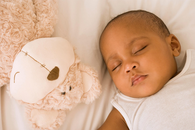 A baby sleeping while hugging a plush toy