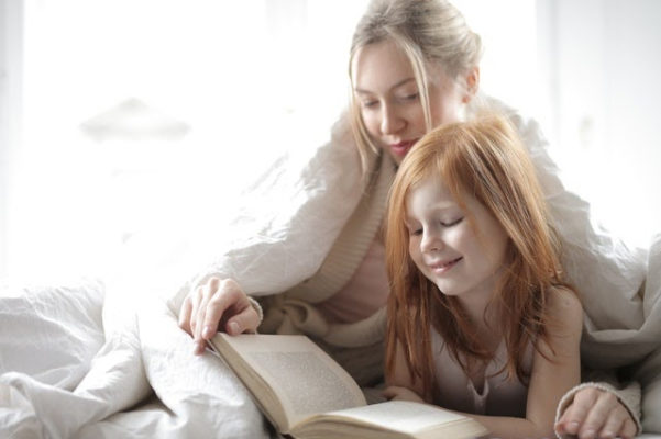 A mother reading a bedtime story to her daughter