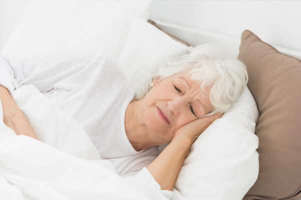 An elderly woman asleep in bed