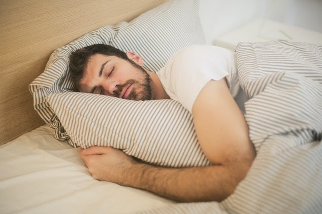 An adult man sleeping in bed