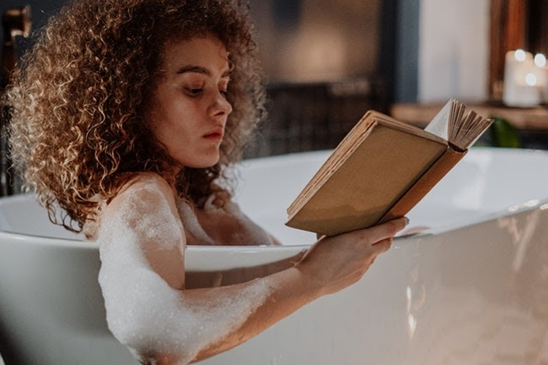 Woman reading a book while in the bathtub